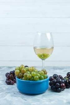汚れた灰色と木製の背景のボウルにワインとブドウのグラスのセットです。側面図。