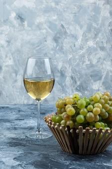 지저분한 석고 배경에 바구니에 와인과 녹색 포도 한 잔의 집합입니다. 측면보기.