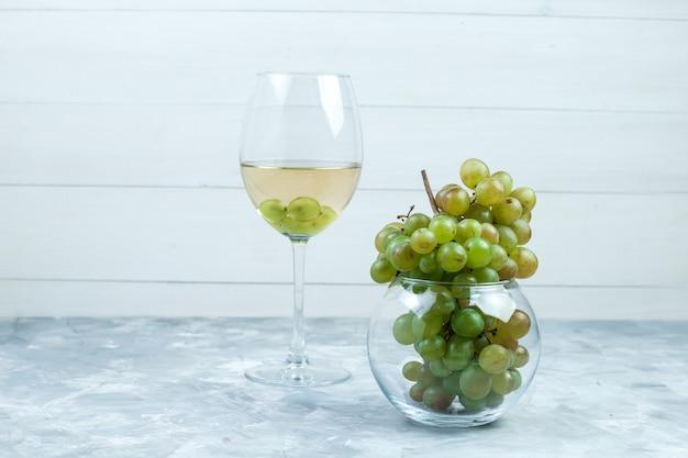 지저분한 회색과 나무 배경에 유리 냄비에 와인과 녹색 포도 한 잔의 집합입니다. 측면보기.