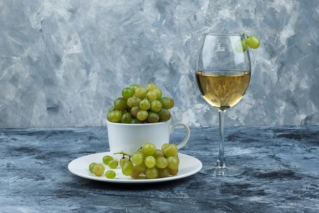 흰색 컵과 지저분한 석고 배경에 접시에 와인과 녹색 포도 한 잔의 집합입니다. 측면보기.