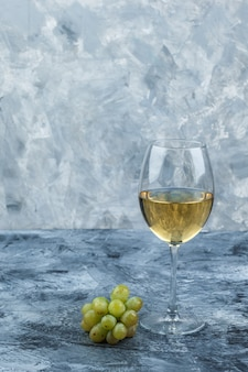 지저분한 석고 배경에 와인과 녹색 포도 한 잔의 집합입니다. 측면보기.