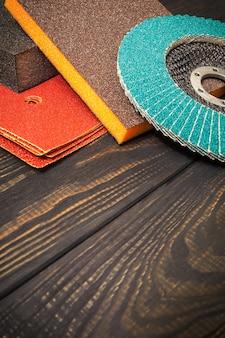 Набор абразивных инструментов и наждачной бумаги на черных старинных деревянных досках