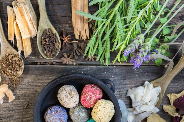 Набор ароматных ладанов и живых цветов и трав на деревенском дереве