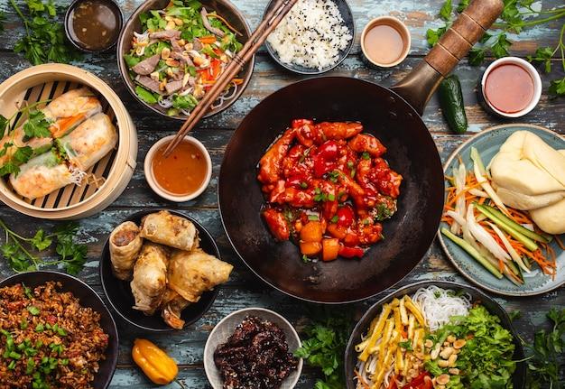 테이블에 다양한 중국 요리 세트: 냄비 팬에 새콤달콤한 닭고기, 대나무 찜기에 딤섬, 스프링롤, 국수, 샐러드, 쌀, 찐 만두, 딥. 아시아 스타일 저녁 식사 또는 뷔페, 최고 전망