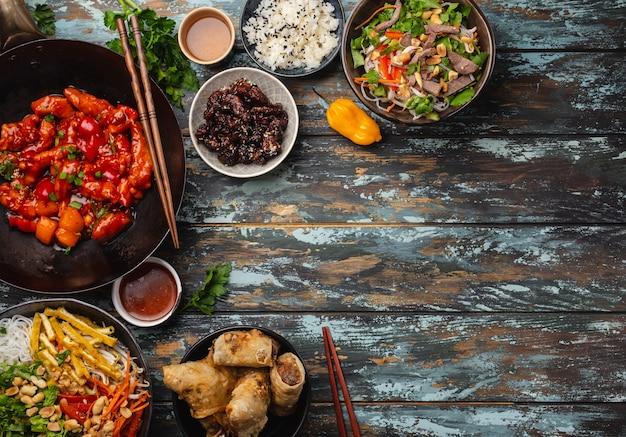 테이블에 다양한 중국 요리 세트: 냄비에 든 달콤하고 신 치킨, 딤섬, 스프링롤, 국수, 샐러드, 쌀, 찐 만두. 최고의 전망과 텍스트 공간이 있는 아시아 스타일 저녁 식사 또는 뷔페
