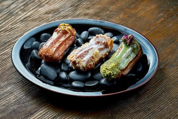 木製のテーブルの黒いプレートにカスタードとトッピングの盛り合わせを添えたフレンチカスタードエクレアの盛り合わせのセット。レストランの食べ物。