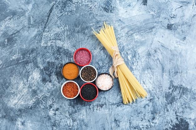 회색 석고 배경에 여러 향신료와 스파게티의 집합입니다. 평면도.