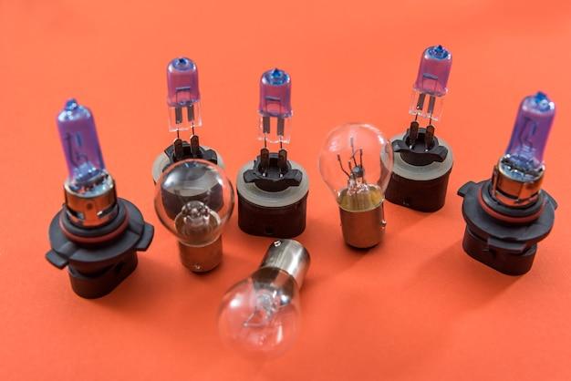 オレンジ色の背景に分離された自動車用電球のセットです。車のライトランプ技術。修理のための機器