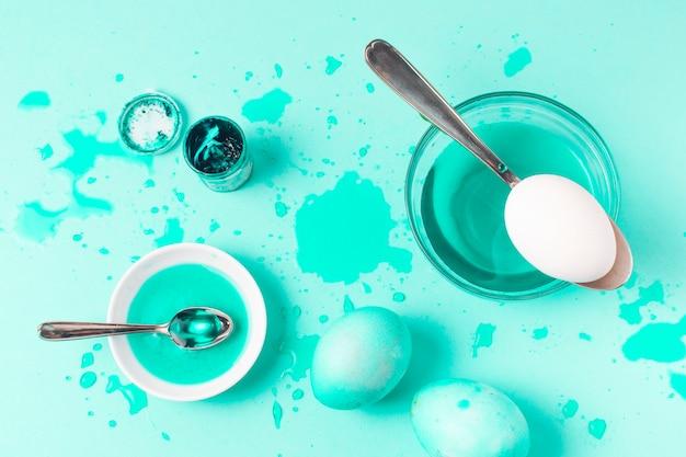 しみ、スプーン、染料の液体の間の紺碧のイースターエッグのセット
