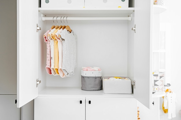 흰색 옷장에 옷걸이에 신생아 소녀와 소년을 위한 아기 바디수트 세트. 어머니, 집 아이 옷장 청소. 최소한의 패션 컨셉입니다.