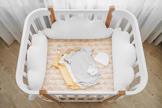 유아용 침대, 요람에서 신생아를 위한 아기 바디수트 세트. 아기 방에 베개 모양의 구름이 있는 흰색 나무 아기 침대. 어린이 침대의 상위 뷰