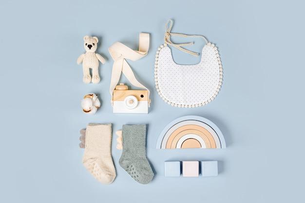 밝은 파란색 배경에 소년을 위한 아기 물건과 액세서리 세트. 귀여운 양말, 턱받이 및 장난감. 베이비 샤워 개념입니다. 패션 신생아입니다. 평평한 평지, 평면도