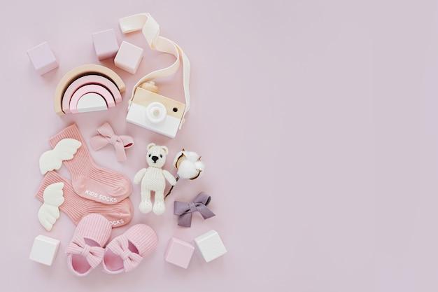 파스텔 배경의 소녀를 위한 아기 물건과 액세서리 세트. 분홍색 양말, 신발, 장난감. 베이비 샤워 개념입니다. 패션 신생아입니다. 평평한 평지, 평면도