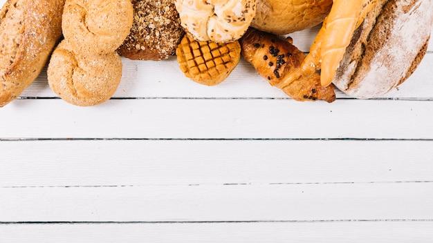 나무 흰색 테이블에 구운 빵 세트 무료 사진