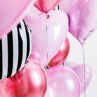 ハートと丸いピンクの形で風船のセットし、コピースペースと明るい背景にストライプします。