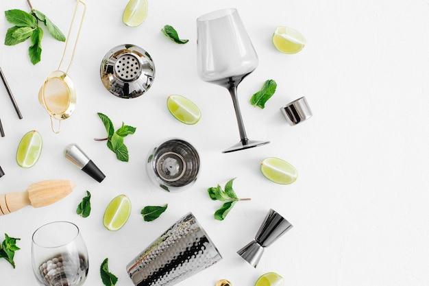 カクテル作りのためのバーアクセサリーのセット。シェーカー、ジガー、ガラス、スプーン、その他のバーツール。背景にライムとミントの葉が付いています。