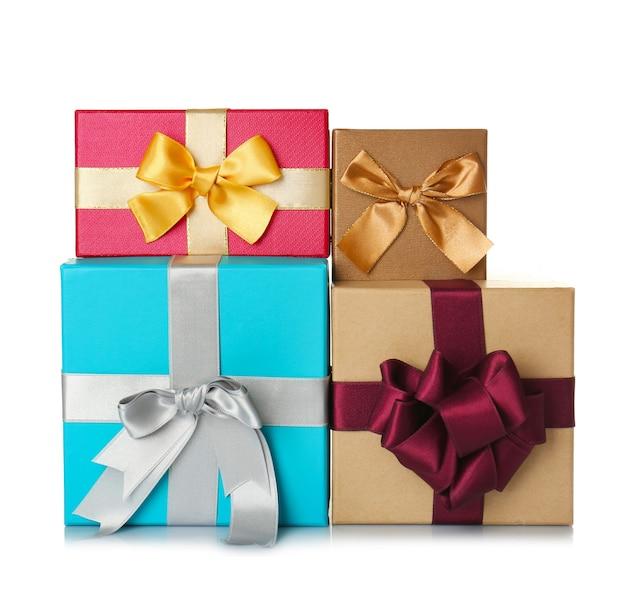 Набор красивых подарочных коробок с чудесными бантами из блестящих лент на белом фоне