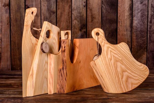 나무 테이블에 아름 다운 나무 절단 보드의 집합입니다. 부엌에서 요리하기