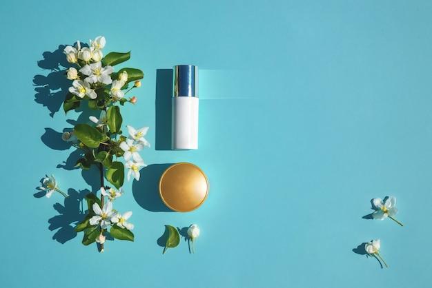 フラットな美容製品のセットは、花と青い背景の上に横たわっていた。自然化粧品のコンセプト。美容液、クリームスキンケア、ミニマルスタイル