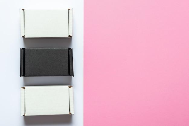ピンクのテーブル、上面図、コピースペースに黒と白のカートンボックスのセット
