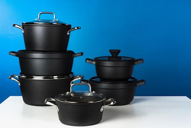 Набор черной посуды на синем фоне вид спереди