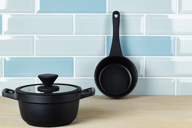 Набор черной посуды на кухонном столе, вид спереди