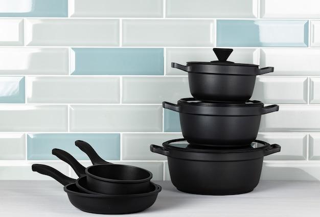Набор черной посуды на кухонном столе