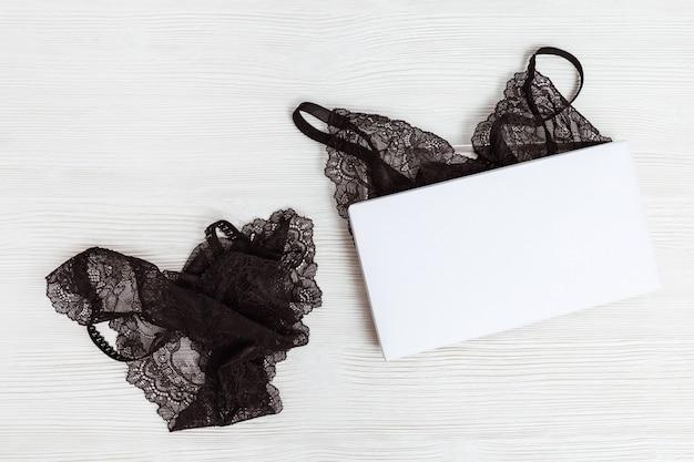 Комплект черного белья в белой коробке. макет. модное женское нижнее белье на деревянных фоне.