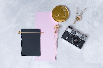 Set of blooms near papers, rings on round and retro camera