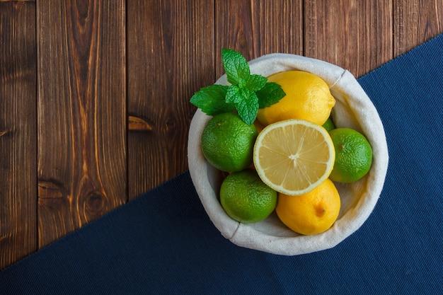Набор голубой ткани и лимонов в корзине на деревянной поверхности. вид сверху. место для текста