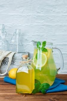 木製と白の表面に青い布、空のボトル、レモンジュースのデカンタのセット。側面図。あなたのテキストのための空きスペース