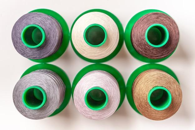 白い背景の上面図に異なる色の糸のボビンとかせのセット