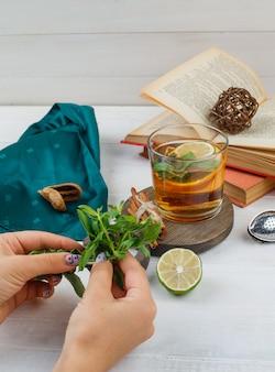 木の板に本、レモン、ミント、緑のスカーフとハーブティーとシナモンのセット