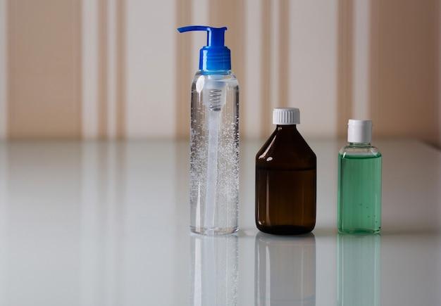 손 위생과 코로나 바이러스 보호를 위한 소독 젤과 알코올이 있는 병 세트. 텍스트를 위한 공간
