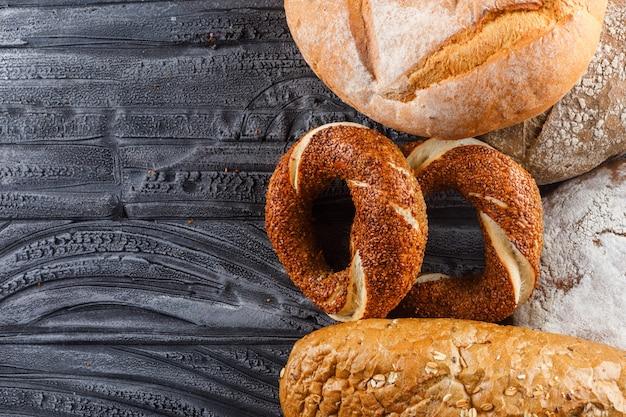 灰色の木製の表面にパンとトルコのベーグルのセット。上面図。テキスト用の空き容量