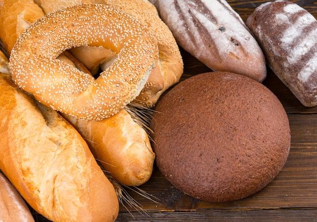 ダークウッドのテーブルにゴマの種のベーグル、バゲット、ロールパン、職人のパンの例とパンのセット
