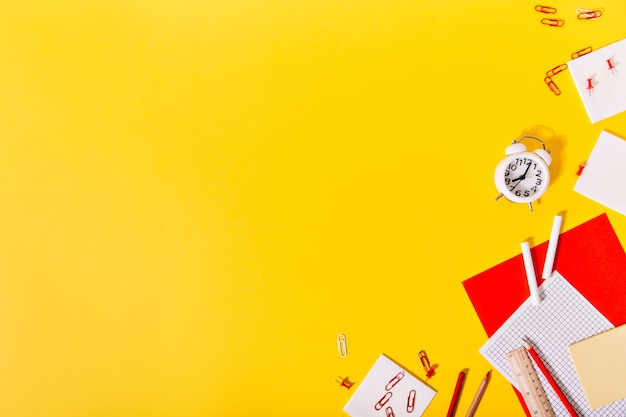 オレンジ色の壁に明るい学校の文房具のセット