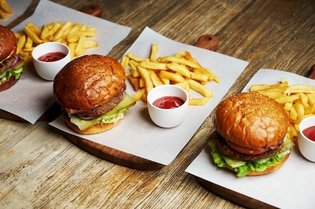 フライドポテトとケチャップソースのハンバーガーのセット。木製のテーブルの背景に大きなハンバーガーとフライドポテト。ファーストフードセットの背景。レストランのハンバーガーメニュー