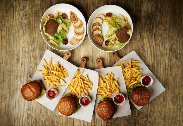 감자 튀김과 케첩 소스와 함께 햄버거 세트. 큰 햄버거와 감자 튀김 나무 테이블 배경. 패스트 푸드는 배경을 설정합니다. 레스토랑 버거 메뉴