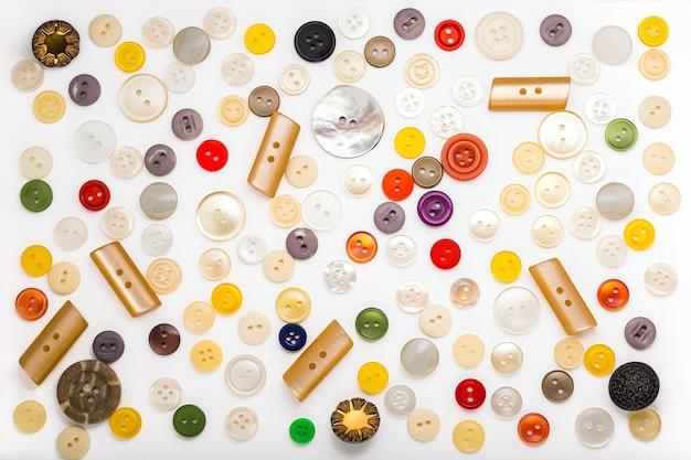 白のさまざまな色、形、素材のボタンのセット