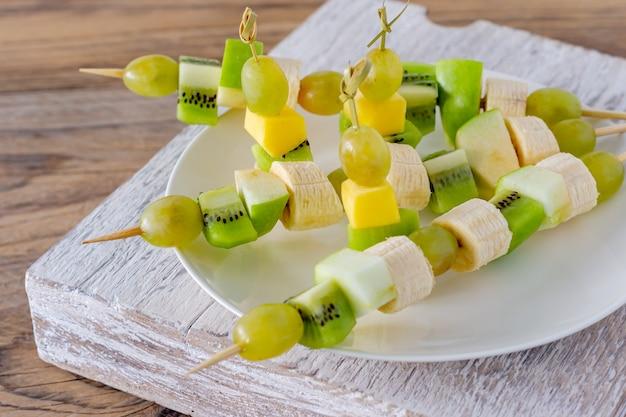 Набор канапе с фруктами, ягодами на белой тарелке на деревянном фоне.