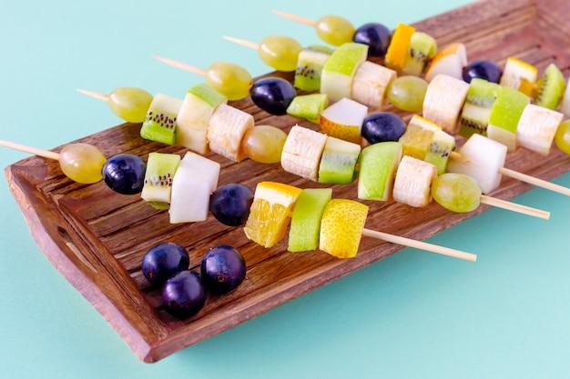 Набор канапе с фруктами, ягодами на деревянной тарелке на синем фоне.