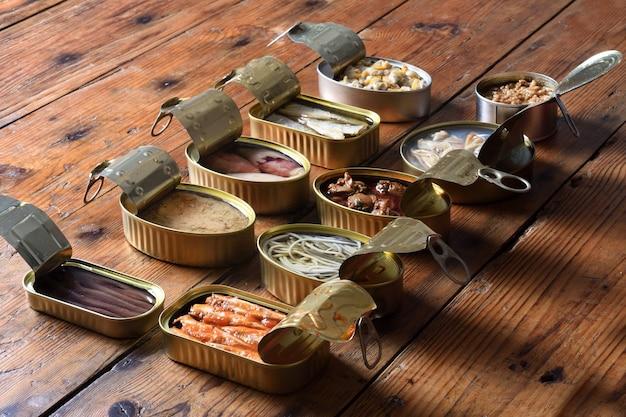 Набор банок с рыбой и морепродуктами на деревянных, лицом к лицу