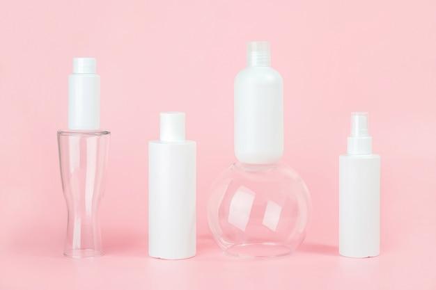 Набор косметических средств по уходу за кожей, лицом, телом или волосами. белые пустые косметические бутылки и трубки на стеклянных подиумах, розовом фоне. спа косметическая концепция красоты.