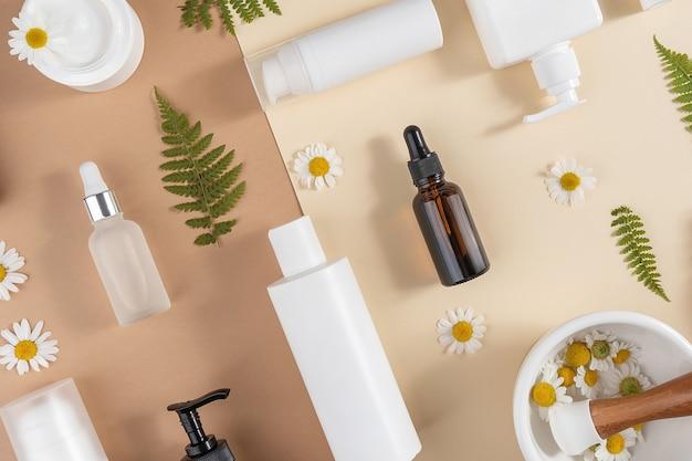 케어 화장품 세트입니다. 다양한 병, 화장품이 든 튜브, 카모마일 꽃, 고사리 잎, 그리고 베이지색과 갈색 배경에 유봉이 있는 모르타르 그릇. 뷰티 개념입니다. 평면도 평면도.