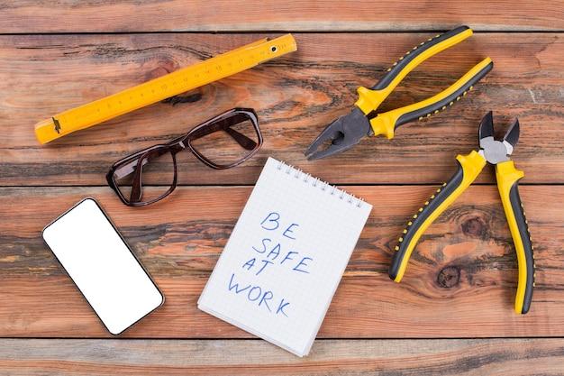 木製の織り目加工の机の上の大工作業ツールスマートフォンメガネのセット