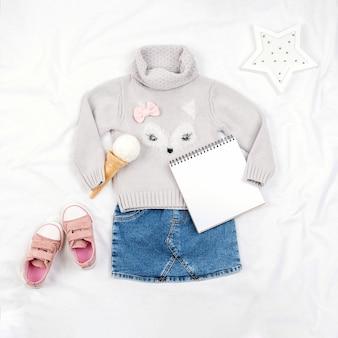 カジュアルな子供服、靴、アクセサリー、白い背景の上のオープンメモ帳のセットです。ファッションガールルックブックconsept。ニットセーター、デニムスカート、スニーカー、アイスクリームコーン。上面図、フラットレイモックアップ。