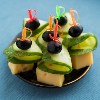 Set of cheese, olive and cucumber on plastic skewer on plate