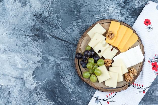 石膏と木片の背景にチーズ、クルミ、キッチンタオル、ブドウのセットです。フラットレイ。
