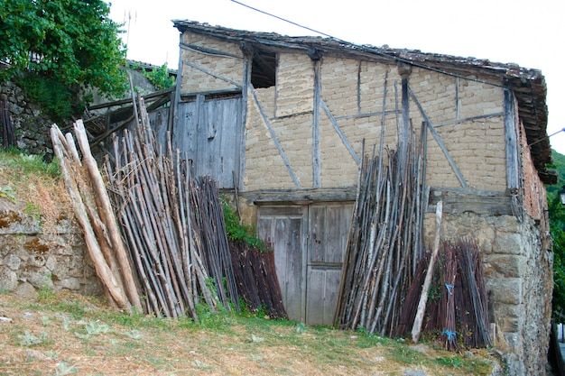 어도비와 목재 외관이있는 오래된 집에 밤나무 나무 로그 세트